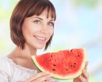 Schöne Frau, die Wassermelone isst Stockbild