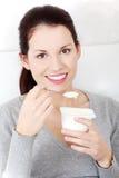 Schöne Frau, die zu Hause einen Joghurt isst. stockfotos