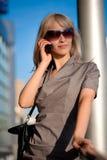 Schöne Frau, die zum Mobiltelefon benennt Lizenzfreie Stockbilder