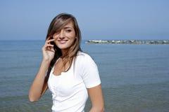 Schöne Frau durch das Meer mit einem Handy Lizenzfreies Stockbild