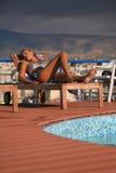 Schöne Frau durch Swimmingpool Stockfotografie