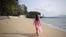 Schöne Frau in einem langen sich entwickelnden rosa Kleid geht das Gehen um das Spinnen auf den Strand auf den Felsen Nahaufnahme stockfoto