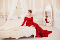 Schöne Frau in einem roten Kleid Stockbilder