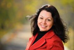 Schöne Frau in einem roten Mantel Lizenzfreies Stockfoto