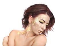 Schöne Frau geschmückt mit Goldblatt-Kosmetik Stockbild