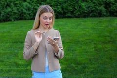 Schöne Frau hält Handy und betrachtet Schirm und drückt aus Stockfotografie