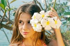 Schöne Frau hinter den Blumen Stockfotografie