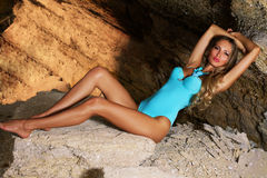 Schöne Frau im blauen Bikini auf dem Felsen Lizenzfreie Stockfotos