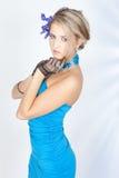Schöne Frau im eleganten Kleid mit blauen Blumen Lizenzfreies Stockbild