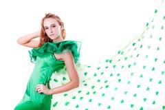 Schöne Frau im Grün und eine Dusche der Shamrocks im März Stockfotos