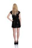 Schöne Frau im reizvollen schwarzen Kleid, das mit steht   Lizenzfreie Stockfotos