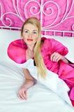 Schöne Frau im rosafarbenen Kleid auf Bett Lizenzfreie Stockfotos