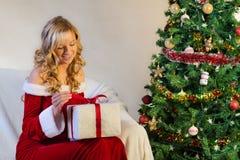 Schöne Frau im Rot entpacken Weihnachtsgeschenk Lizenzfreies Stockbild