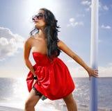 Schöne Frau im roten Kleid auf dem Ufer stockfoto