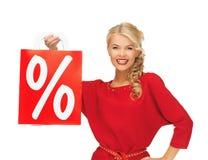 Schöne Frau im roten Kleid mit Einkaufstasche Lizenzfreies Stockfoto