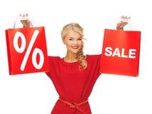 Schöne Frau im roten Kleid mit Einkaufstasche Lizenzfreie Stockfotos