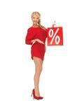 Schöne Frau im roten Kleid mit Einkaufstasche Stockfotografie