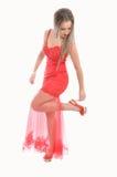 Schöne Frau im roten Kleid ordnet ihre Schuhe an Stockbilder