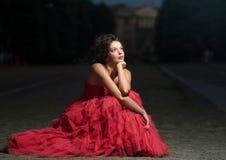 Schöne Frau im roten Kleid am Sonnenuntergang Lizenzfreie Stockfotografie
