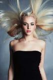 Schöne Frau im schwarzen Kleid Reizvolles blondes Mädchen Schönes gesundes Haar Polnisch der Nägel mit dem nailfile Stockfotos