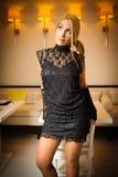 Schöne Frau im schwarzen Kleiderschauen Stockfoto