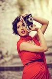 Schöne Frau im städtischen Hintergrund Abbildung der roten Lilie Lizenzfreies Stockbild
