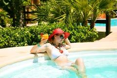 Schöne Frau im Swimmingpool mit Cocktail Lizenzfreies Stockbild