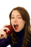 Schöne Frau isst und Apfel und blinzelt Stockbild