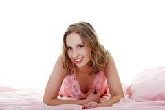 Schöne Frau liegt im Bett und im Lächeln. Stockbild