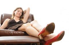 Schöne Frau Lounging in einem Lehnsessel Stockfotografie