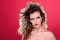 Schöne Frau mit dem lockigen Haar auf Rot lizenzfreie stockbilder