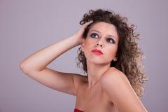 Schöne Frau mit dem lockigen Haar, das Haar anhalten stockbilder