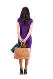 Schöne Frau mit dem Shoping sackt das Betrachten der Wand ein. Stockfotografie