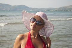 Schöne Frau mit dem Strohhut, der nahe Strand aufwirft stockbilder