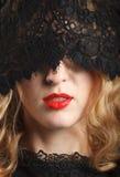 Schöne Frau mit den roten Lippen und Spitzemaske Lizenzfreie Stockbilder