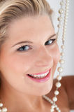 Schöne Frau mit den weißen Zähnen und den Perlen Stockfoto