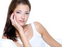 Schöne Frau mit der sauberen Haut, die auf Sofa sitzt Stockbild