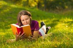 Schöne Frau mit einem Buch im Park Stockbilder