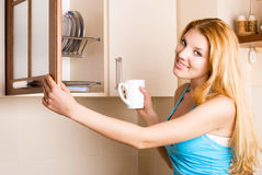 Schöne Frau mit einem Cup in der Küche Stockfotografie