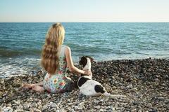 Schöne Frau mit einem Hund auf dem Strand Stockfotografie