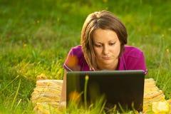 Schöne Frau mit einem Laptop im Park Stockbild