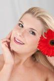 Schöne Frau mit einer gesunden Haut und einer Blume Stockfoto