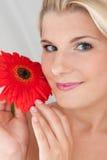 Schöne Frau mit einer gesunden Haut und einer Blume Lizenzfreie Stockfotografie