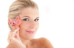 Schöne Frau mit einer gesunden Haut und einer Blume Lizenzfreie Stockfotos