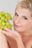 Schöne Frau mit einer gesunden Haut und Trauben Lizenzfreies Stockfoto