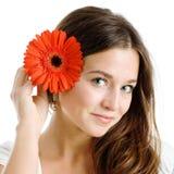 Schöne Frau mit einer hellen roten Blume Lizenzfreie Stockfotografie