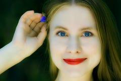 Schöne Frau mit einer kleinen blauen Blume Lizenzfreie Stockbilder