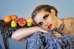 Schöne Frau mit Federn und Frucht Stockbilder