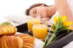 Schöne Frau mit Frühstück im Bett Stockfotografie