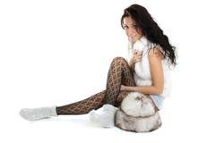 Schöne Frau mit Pelzhutsitzen Stockbilder